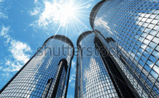 Stock-photo-high-modern-skyscrapers-on-a-background-of-the-blue-sky-and-in-solar-patches-of-light-9558235