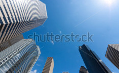 Stock-photo-looking-up-at-a-group-of-modern-office-buildings-77151223
