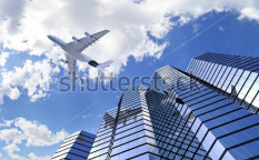 Stock-photo-plane-reflecting-on-modern-building-facade-while-flying-through-the-sky-97869065