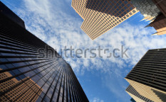 Stock-photo-upward-fish-eye-view-of-tall-skyscrapers-against-a-blue-sky-in-the-downtown-business-area-of-64686028