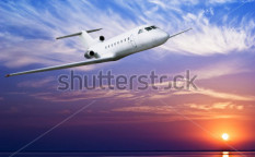 Stock-photo-airliner-flying-above-tropical-sea-at-sunset-63498322