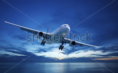 Stock-photo-jet-plane-over-the-sea-at-dusk-93058477