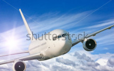 Stock-photo-large-passenger-plane-flying-in-the-blue-sky-72078526