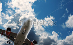 Stock-photo-passenger-jet-against-a-blue-sky-with-white-fluffy-clouds-98542496